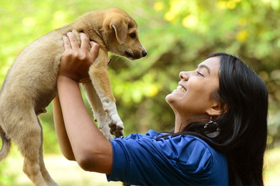 Woman holding up a puppy